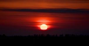 Karmosinröd solnedgång. Arkivfoto