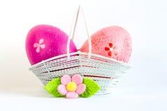 Karmosinröda och rosa påskägg i en korg med rosa färger blommar Royaltyfri Foto