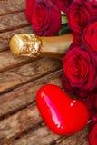 Karmosinröda röda rosor med halsen av champagne Royaltyfria Bilder