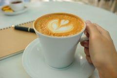 Karmowa tło ręka biznesmena chwyta filiżanka z kawą, pisze Fotografia Stock