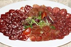 Karmowa taca z salami, kawałkami pokrojony baleron, kiełbasą, pomidorami, sałatką i warzywem, Ciąć - Mięsny półmisek z wyborem - zdjęcie stock