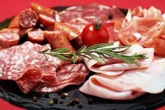 Karmowa taca z wyśmienicie salami, baleronem, świeżymi kiełbasami i ziele, zdjęcia stock