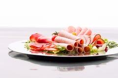 Karmowa taca z wyśmienicie salami, kawałkami pokrojony baleron, kiełbasą, pomidorami, sałatką i warzywem, - Fotografia Royalty Free