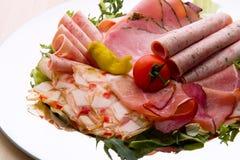 Karmowa taca z wyśmienicie salami, kawałkami pokrojony baleron, kiełbasą, pomidorami, sałatką i warzywem, - Obraz Royalty Free