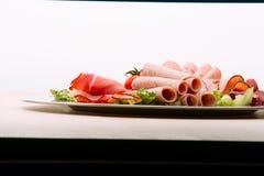 Karmowa taca z wyśmienicie salami, kawałkami pokrojony baleron, kiełbasą, pomidorami, sałatką i warzywem, Zdjęcia Royalty Free