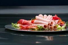 Karmowa taca z wyśmienicie salami, kawałkami pokrojony baleron, kiełbasą, pomidorami, sałatką i warzywem, - Zdjęcia Royalty Free
