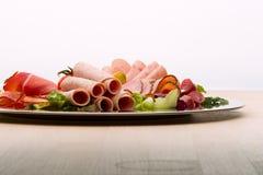 Karmowa taca z wyśmienicie salami, kawałkami pokrojony baleron, kiełbasą, pomidorami, sałatką i warzywem, - Zdjęcia Stock
