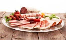 Karmowa taca z wyśmienicie salami, kawałkami pokrojony baleron, kiełbasą, pomidorami, sałatką i warzywem, - Mięsny półmisek z wyb fotografia stock