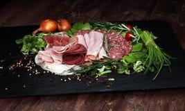 Karmowa taca z wyśmienicie salami, kawałkami pokrojony baleron, kiełbasą, pomidorami, sałatką i warzywem, - Mięsny półmisek z wyb Zdjęcia Stock