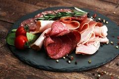 Karmowa taca z wyśmienicie salami, kawałkami pokrojony baleron, kiełbasą, pomidorami, sałatką i warzywem, - Mięsny półmisek z wyb Obraz Stock