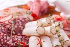 Karmowa taca z wyśmienicie salami, kawałki pokrojony baleron, kiełbasa Tnąca kiełbasa i leczący mięso na uroczystym stole obrazy royalty free