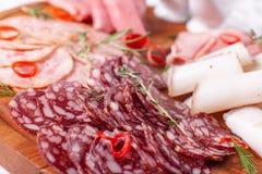 Karmowa taca z wyśmienicie salami, kawałki pokrojony baleron, kiełbasa Tnąca kiełbasa i leczący mięso na uroczystym stole zdjęcia stock