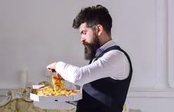 Karmowy doręczeniowy pojęcie Mężczyzna z brody i wąsy chwytami boksuje z smakowitą świeżą gorącą pizzą Macho w klasyków ubraniach Zdjęcia Stock
