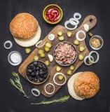 Karmowy hamburger z tuńczyka Karmowym hamburgerem z tuńczykiem, ziele, ogórkami, oliwkami, cebulami i kumberlandem na tnącej desc Fotografia Royalty Free
