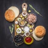 Karmowy hamburger z tuńczyka Karmowym hamburgerem z tuńczykiem, ziele, ogórkami, oliwkami, cebulami i kumberlandem, tnąca deska n Obrazy Royalty Free