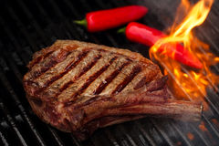 Karmowy mięso - wołowina stek na bbq grilla grillu z płomieniem Zdjęcia Stock