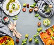 Karmowy tło z kolorowymi pomidorami, mozzarella serem z oliwka olejem i basilem, opuszcza na kuchennym stole, odgórny widok, rama zdjęcie stock