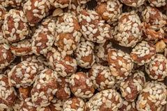 Karmowy tło robić arachidy zakrywający z glazerunkiem i kropiący z sezamowymi ziarnami obraz royalty free