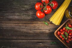 Karmowy tło: suchy makaron, pomidory, oliwa z oliwek i pikantność, Zdjęcia Royalty Free
