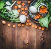 Karmowy tło z organicznie lokalnymi warzywami dla zdrowego czystego łasowania i kucharstwa na nieociosanym drewnianym, odgórnym w Obrazy Royalty Free