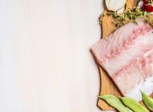 Karmowy tło z Surową rybią polędwicową i świeżą podprawą na białym drewnianym tle, odgórny widok fotografia royalty free