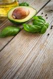 Karmowy tło z avocado, oliwa z oliwek i basilem na starej pogodzie, Zdjęcia Stock