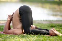 Karna pidasana Yoga Pose Stock Photo
