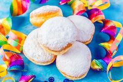 Karnawałów sproszkowani cukrowi donuts z papierowymi streamers obrazy stock