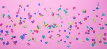 Karnawał, przyjęcie urodzinowe Kolorowi confetti na różowym tle zdjęcie royalty free