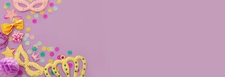 karnawału świętowania partyjny pojęcie z maskowymi i kolorowymi partyjnymi akcesoriami nad purpurowym drewnianym tłem Odgórny wid zdjęcia stock