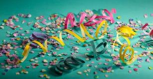 Karneval- eller födelsedagparti, konfettier och serpentines på ljust - grön bakgrund royaltyfria bilder
