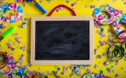 Karneval- eller födelsedagparti Tom svart tavla, konfettier och serpentines på ljus gul bakgrund royaltyfria bilder