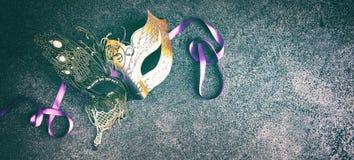 Karneval- eller Mardi Gras maskering på texturerade grå färger royaltyfria foton