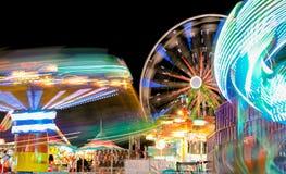 Karneval och Ferris Wheel på nattsnurrljus royaltyfri foto