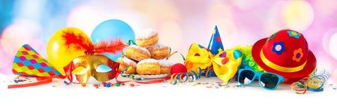 Karneval oder Partei mit Schaumgummiringen, Ballone, Ausläufer und Konfettis und lustiges Gesicht lizenzfreies stockfoto