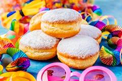 Karneval pudrade sockerdonuts med pappers- banderoller royaltyfri foto