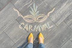 Karneval som är skriftlig på den gråa trottoaren med kvinnaben i gula skor arkivbild