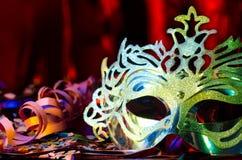 Karnevalet maskerar med en silkeslen röd bakgrund Arkivfoto