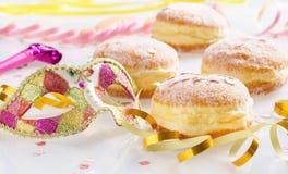 Karnevalet pudrat socker lyftte donuts med pappers- banderoller och den venetian maskeringen Arkivbilder