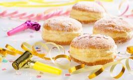 Karnevalet pudrat socker lyftte donuts med partiflugan och pappers- banderoller Royaltyfri Bild