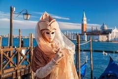 karnevalmaskering mot gondoler i Venedig, Italien Royaltyfri Fotografi