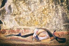 Karnevalmaskering på guld- suddighetsbakgrund Royaltyfri Foto