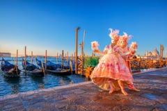 Karnevalmaskeringar mot gondoler i Venedig, Italien Arkivbilder