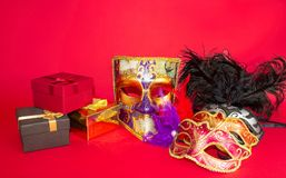 Karnevalmaskeringar och gåvor på en röd bakgrund fotografering för bildbyråer