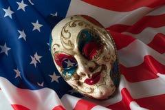 Karnevalmaskeringen ligger på amerikanska flaggan Arkivfoton