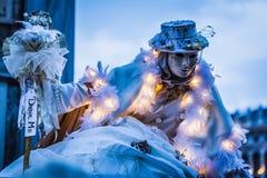 Karnevalrumlaren i upplyst dräkt som skymning faller, Venedig, Royaltyfria Bilder