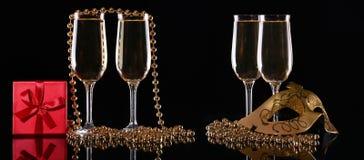 Karnevalsmaske und -gläser mit Champagner auf einem dunklen Hintergrund Lizenzfreies Stockfoto