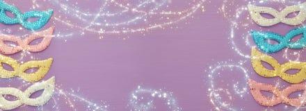 Karnevalspartei-Feierkonzept mit buntem Pastellrosa, Gold, Silber und blauen Masken über purpurrotem hölzernem Hintergrund Beschn stockfotografie
