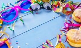 Karnevalsrahmen mit buntem Zubehör auf blauem hölzernem Hintergrund Stockbilder