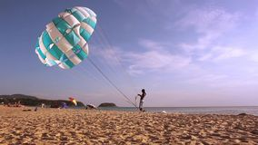 KARON BEACH,PHUKET,THAILAND,2 OF May 2015. Man holding a parachute in the wind on the beach. Background. Karon is one of the most popular beaches of Thailand stock video